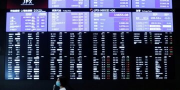 A TV reporter stands in front of a large screen showing stock prices at the Tokyo Stock Exchange after market opens in Tokyo, Japan October 2, 2020. REUTERS/Kim Kyung-Hoon/File Photo