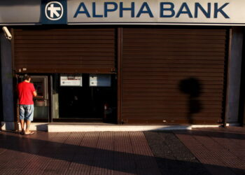A man withdraws money at an Alpha Bank branch ATM in central Athens, Greece, July 19, 2015.