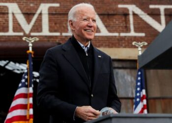 FILE PHOTO: U.S. President-elect Joe Biden holds his face mask as he campaigns on behalf of Democratic U.S. Senate candidates from Georgia Jon Ossoff and Raphael Warnock, ahead of their January 5 runoff elections, during a drive-in campaign rally at Pullman Yard in Atlanta, Georgia, U.S., December 15, 2020. REUTERS/Mike Segar