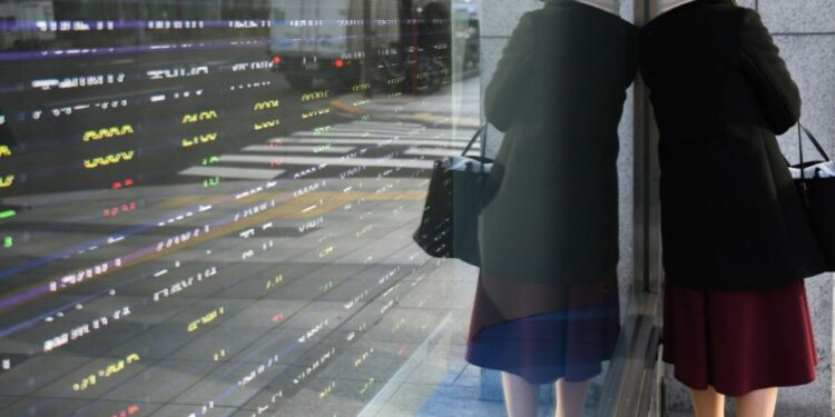 A pedestrian stands against an electronic stock board outside a securities firm in Tokyo. Photographer: Noriko Hayashi/Bloomberg