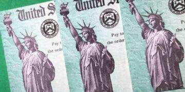 Treasury checks for coronavirus relief; Closeup view against green background