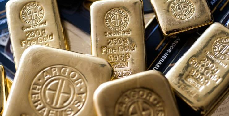 An Argor-Heraeus SA branded two hundred and fifty gram gold bar, center, sits in this arranged photograph at Solar Capital Gold Zrt. in Budapest, Hungary.