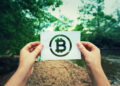 Woman hands holding a paper sheet with Bitcoin symbol in the middle of the nature with a river flowing near the forest. Eco crypto and digital currency concept.